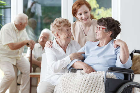 Kaukasische verpleegster en de vriend die van haar patiënt oudere dame in rolstoel steunen