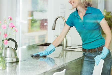 Professional house cleaning service concept, smiling woman wiping down marble kitchen countertop using domestic cleaner, cloth and rubber household gloves
