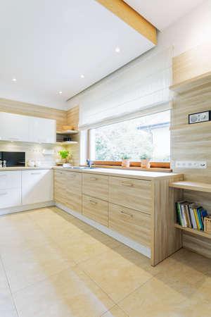 Cuisine claire et moderne avec mobilier blanc et vue sur le jardin Banque d'images - 87211269