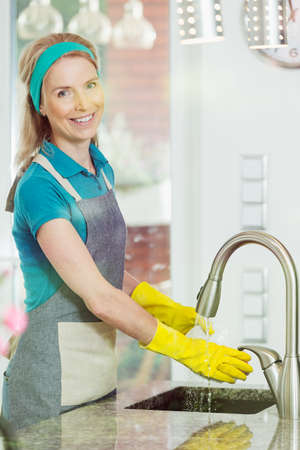 Female housekeeper rinsing dishes under running water in the sink in modern house, smiling at camera wearing yellow household gloves