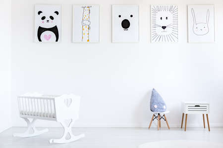 White cradle in babys bedroom with blue pillow on small chair next to cabinet against wall with animal posters gallery