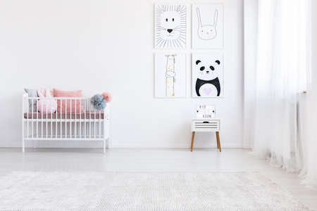 Panda drawing on wall above white cabinet in girl's bedroom with pink pillows on bed Foto de archivo