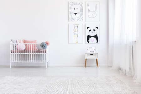 Panda die op muur boven wit kabinet in de slaapkamer van het meisje met roze hoofdkussens op bed trekt