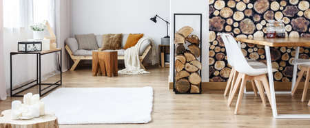Warm multifunctional room with sofa and dining table against wall with log wallpaper Stockfoto