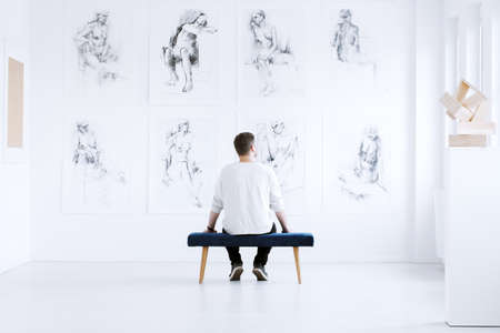 Man relaxing in art gallery while sitting on stool in front of white wall with drawings. Art gallery concept Stok Fotoğraf - 89249899