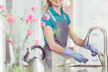 countertop: Domestic service and housekeeping concept, happy blonde lady in apron cleaning kitchen sink, close-up of hands in rubber gloves holding sponge under running water