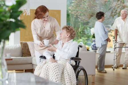 Kind and helpful nurse handing white cup of coffee to elder lady in wheelchair