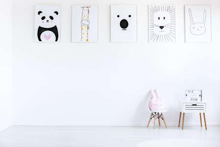 Almohada en colores pastel en la pequeña silla al lado del gabinete contra la pared con dibujos autistic niño en sala blanca, concepto de espacio de copia Foto de archivo - 87211303