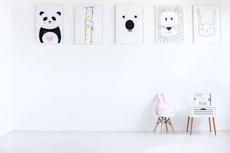 Pastel pillow on small chair next to cabinet against wall with autistic kid drawings in white room, copy space concept Stock Photo