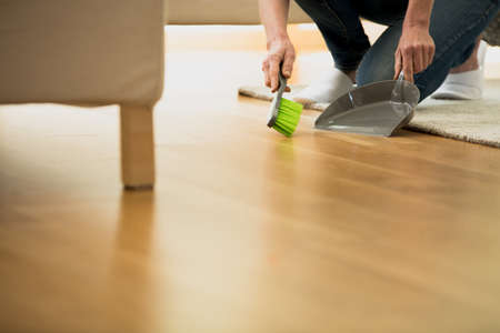 Housekeeping, cleaning and housework concept, copy space and close-up of person using brush and dustpan on the wooden floor