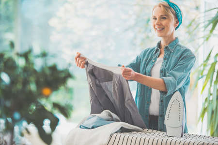 Smiling beautiful middle-aged housewife holding wrinkled clothes after washing, woman sorting clean laundry on ironing board