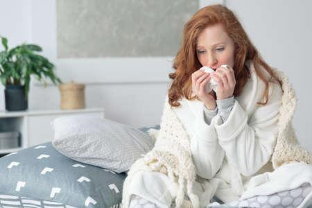 Ellendig vrouw zittend op het bed gewikkeld in deken, ziek gevoel met griep, met koorts en blazen loopneus met zakdoek