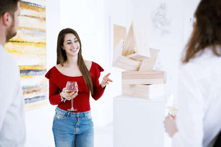 Pretty patron of art talking about painting collection during exhibition in art center Stock Photo