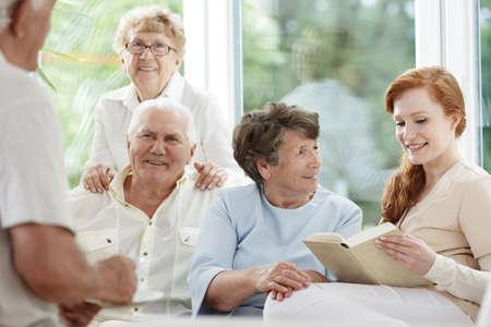 Groep van senioren plezier luisteren naar verzorger lezen tijdens vrije tijd