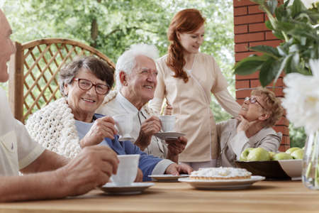 Elder people sitting by the table with tea cups during meeting outdoors Stock Photo