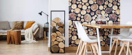 Firewood next to white chairs and dining table with liqueurs in room with sofa and wooden stool Stockfoto