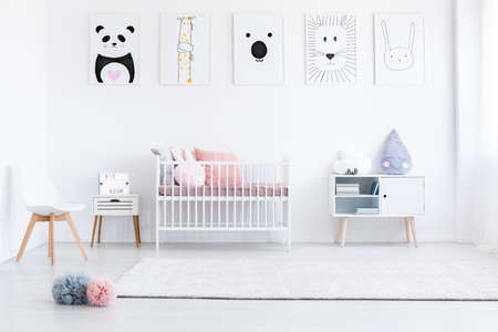 Girl's bedroom with pastel pompons on floor and pink pillows on bed against wall with drawings Banco de Imagens - 87211328