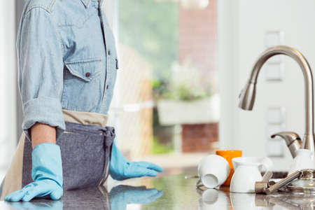 Cropped image of woman in apron wearing cleaning rubber gloves standing at the kitchen sink full of dirty dishes Stock Photo