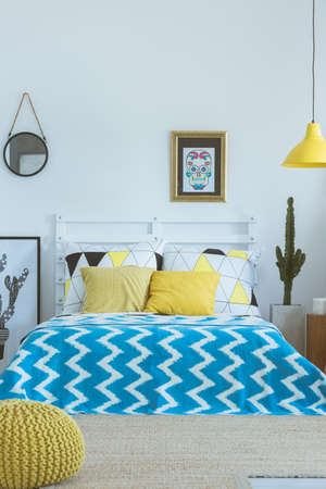 Yellow pouf in front of king-size bed with blue patterned coverlet and yellow pillows Stock Photo