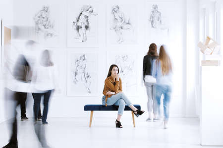 Tourist woman sitting on stool while visiting local art gallery with drawings and sculpture Stok Fotoğraf - 87211338