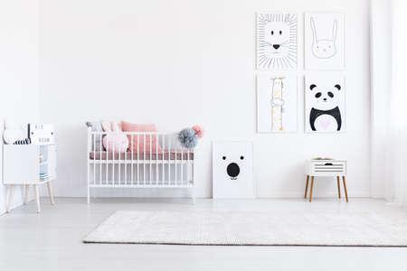 Dierlijke tekeningengalerij in de slaapkamer van het meisje met roze hoofdkussens op bed en witte kast