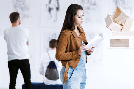 Woman reading guidebook while visiting contemporary art gallery with wooden sculpture