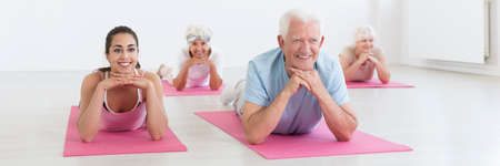 Panorama view, group of positive senior people lying on fitness mats stretching during sport class with young yoga instructor at gym Stock Photo