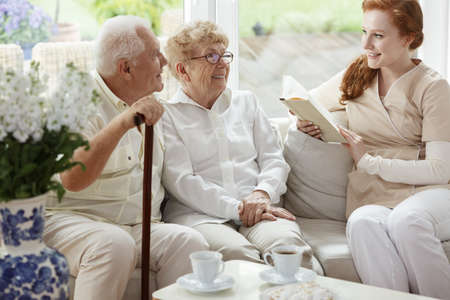 Elder married couple sitting on the couch and smiling at nurse with a book
