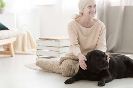 Smiling eldery woman with cancer spending time with black dog during animal assisted therapy