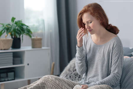 Young woman sick with flu having headache sitting on the bed suffering from runny nose and high fever