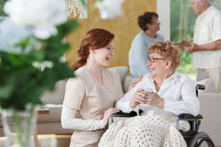 Young Caucasian nurse in uniform smiling and talking to a senior in wheelchair