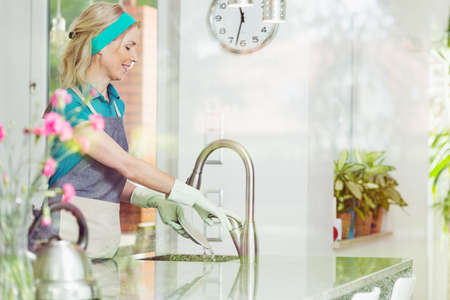 Smiling mature housewife washing the dishes in kitchen sink at her big modern home wearing apron, rubber gloves and headband Stock Photo