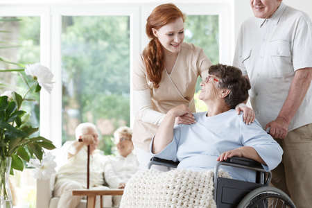 Caucasian caregiver holding disabled lady's shoulders and her husband pushing wheelchair Stock Photo