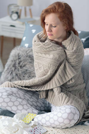 Young ill woman wrapped in a warm blanket feeling cold sitting at home with pills for sore throat and tissues