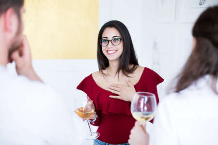 Smiling artist woman drinking wine and talking about own gallery during meeting with audience
