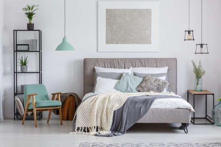 Silver painting above king-size bed with knit beige blanket in adorable bedroom with mint retro chair