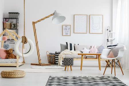 白いデザインの椅子と子供部屋に木製のテーブルの横にある黒と白のスツール