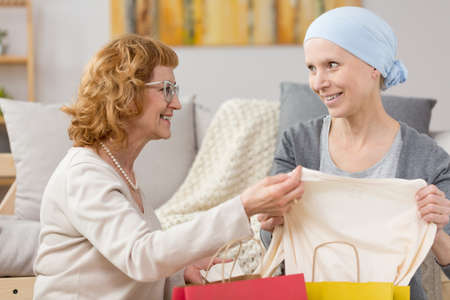 Tumor survivor receiving a gift of new clothes from her sister Stock Photo