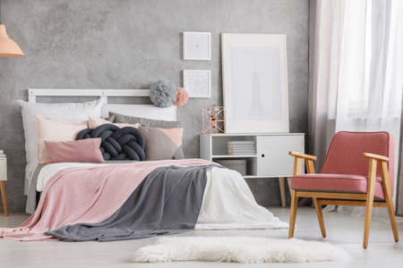 White fur and powder pink design chair in unique pastel bedroom with copper lamp on cupboard