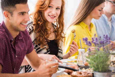 Young happy redhead woman enjoying vegetarian dinner with family members, vegetarian family eating together