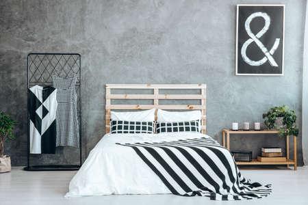 Zwei Kleider auf einem Kleiderbügel stehen neben einem hölzernen Kingsize-Bett Standard-Bild - 87277539
