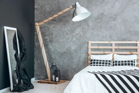 White mirror with black blanket standing against the wall next to wooden oversize lamp