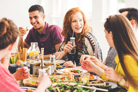 Group of mixed-race people celebrating vegan party at home, sitting at colorful table full of healthy snacks, salads and organic dishes Stockfoto