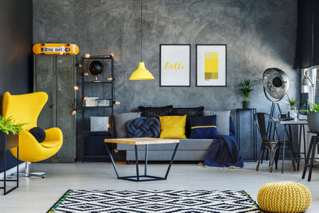 Yellow lamp above table in living room with grey sofa, yellow pouf and designer chair