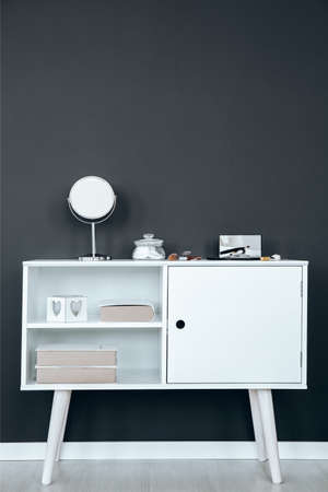 White wooden cupboard with small mirror and make-up brushes on it