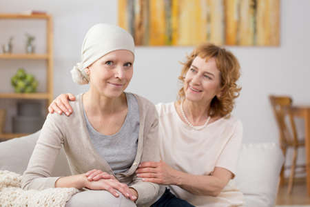 Breast cancer survivor wearing a headscarf, and sitting on a couch with a friend Stock Photo
