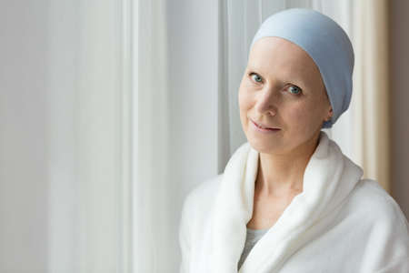 Breast cancer survivor after chemotherapy in a robe, looking positive and hopeful