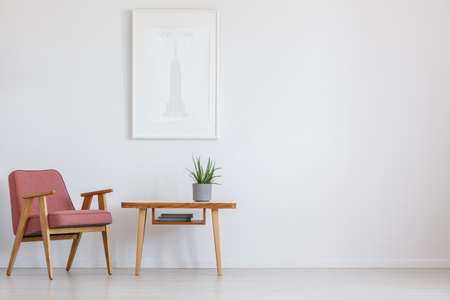 Simple painting above wooden table with plant in grey pot next to powder pink vintage chair