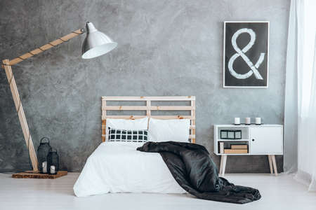 Black shiny coverlet thrown on the wooden bed in modern room Stock Photo