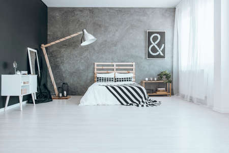 Wooden oversize lamp in stylish bedroom with textured wall Zdjęcie Seryjne